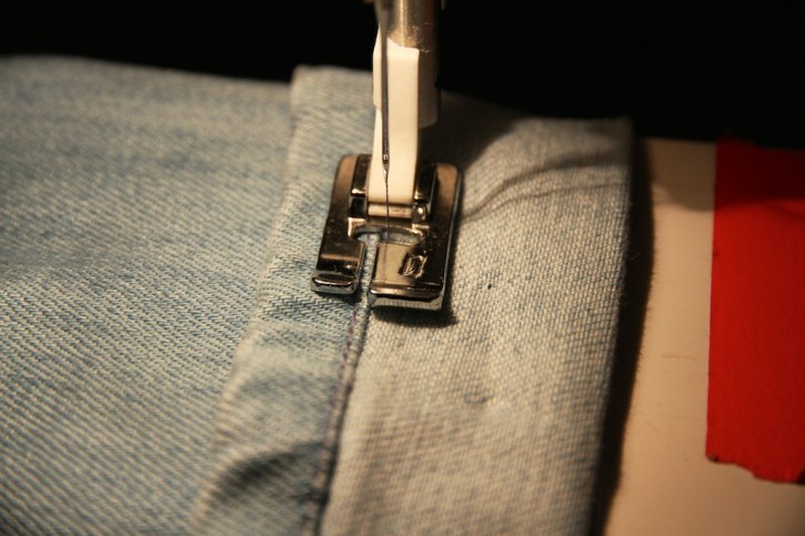 The needle is positioned right next to the hem. You don't want to sew on the hem, so an edge stitching foot is useful.